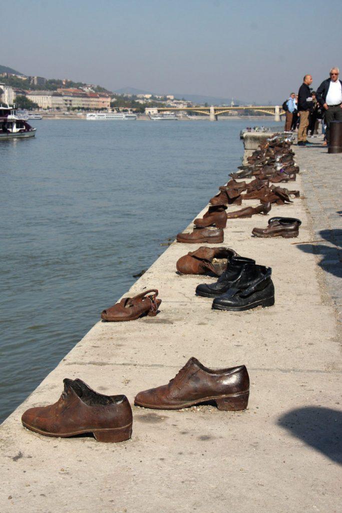 Schuhe aus Metall und Touristen am Donauufer.